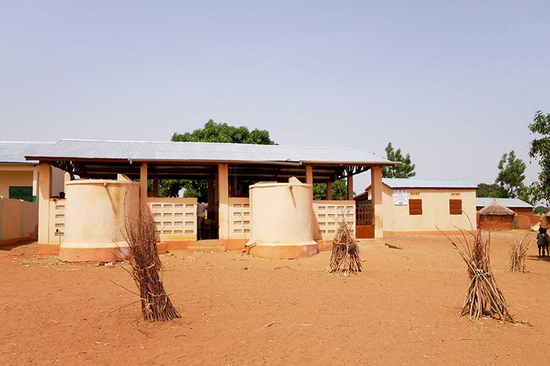 La cantine avec les citernes et le batiment de stockage à côté, Nagou, Togo